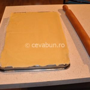Întindeţi fiecare bucata de aluat pe o foaie de hârtie de copt, pe fundul unei tăvi