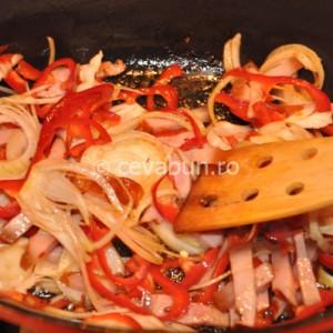 Rumeniţi în grăsimea din cratiţă ceapa, ardeiul şi costiţa de porc