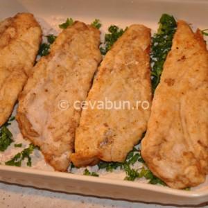 Montaţi peştele într-o tavă unsă cu unt, peste ceapă şi pătrunjel