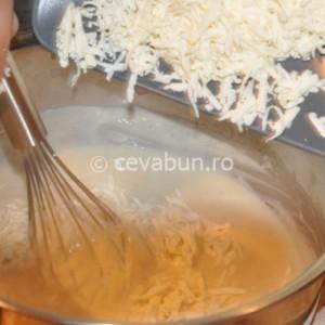 Adăugaţi brânza rasă în vasul luat de pe foc